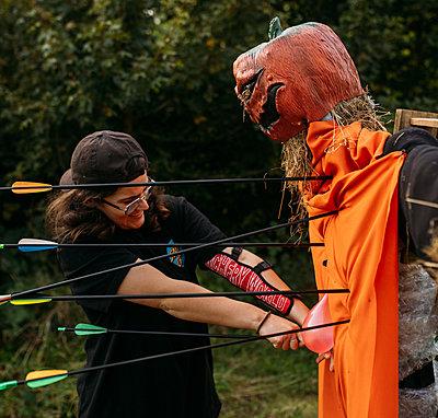Guest pulls an arrow out of pumpkin scarecrow archery target