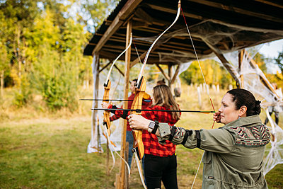 Guests get ready to shoot their arrows underneath outdoor sheltered wooden station