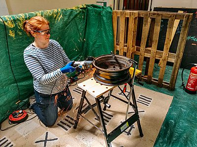 woman in a workshop using a power tool to make a metal fire pit
