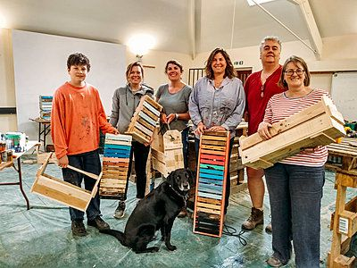 happy group in a workshop holding furniture made from pallets