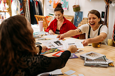 Guests laugh exchanging design cheat sheets during workshop