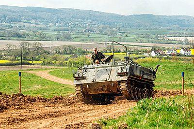 men in a tank driving through a field