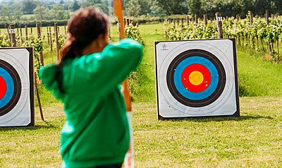 woman outside firing an arrow at an archery target