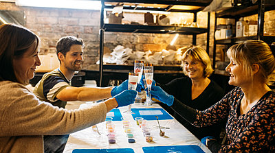 Guests toast Prosecco glasses during resin workshop in an industrial style studio