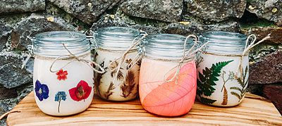 handmade candles in decorative jars on a table