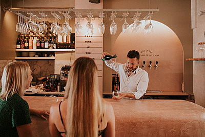 man pouring wine for guests in a wine bar