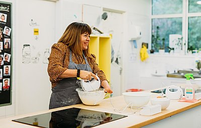 Briony May Williams in a kitchen making a cake