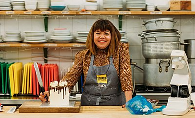 Briony May Williams in a kitchen stood next to a cake