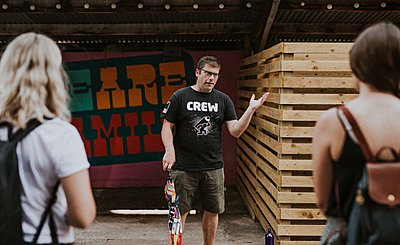 man stood in front of graffiti talking to a group