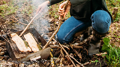 person cooking over fire in a woodland