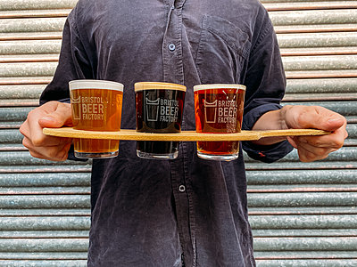 man holding a tasting flight of Bristol beer factory beers