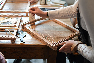 hands weaving on a small loom